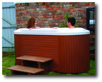 Two people in oval hot tub outside that is on display in showroom of Mokena pool store.