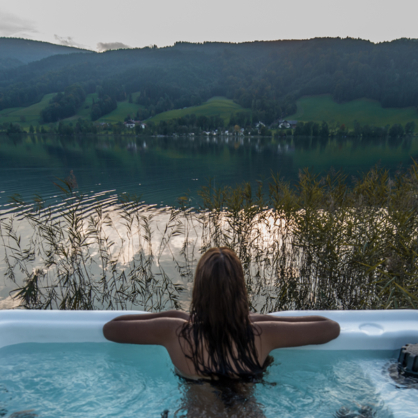 Woman in hot tub looking at mountain view, that was professionally installed by Schererville hot tub contractors.