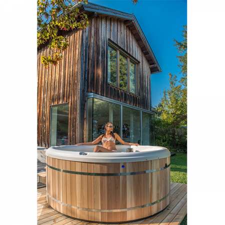 Woman relaxing in hot tub outside on wood deck, that was professionally built by Valparaiso spa contractors.