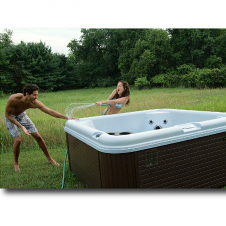 A couple filling up a hot tub, that was professionally installed by Frankfort hot tub contractors.