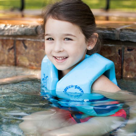 Girl with swim vest in pool, Valpo inground pool business has the proper pool products to help the water quality of a swimming pool.